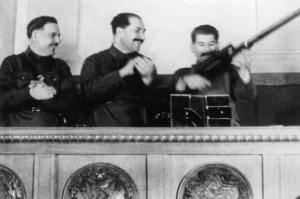 Stalin im Präsidium des siebzehnten Parteitags mit einem Gewehr, das ihm eine Arbeiterdelegation geschenkt hatte
